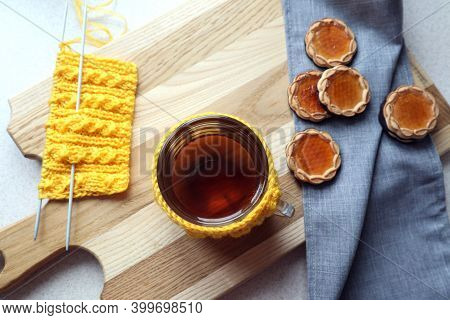 A Cup Of Tea In A Knitted Yellow Outfit With Needlework And Homemade Cookies On A Gray Napkin, Top V