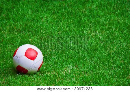 A red and white soccer ball on grass. Uma bola de futebol branca e vermelha na grama.