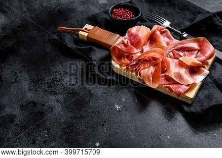 Spanish Jamon Serrano, Ham. Black Background, Top View, Space For Text