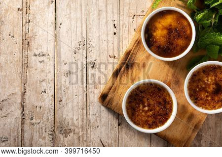 Homemade Creme Brulee In Bowl On Wooden Table. Top View. Copy Space
