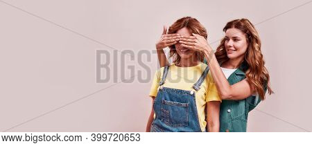 Portrait Of Two Attractive Twin Sisters In Casual Wear. Young Girl Covering Sisters Eyes With Hands