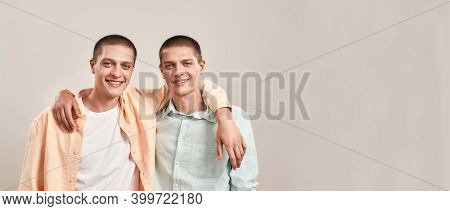 Two Happy Young Twin Brothers Hugging And Smiling At Camera While Posing Together Isolated Over Beig