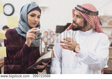 Arab Man And Woman Working In Offce. Coworkers Are Taking Notes On Glass Board.