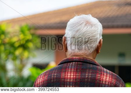 Back View Of An Elderly Asian Man Looking At His Home While Standing In A Garden. Concept Of Aged Pe