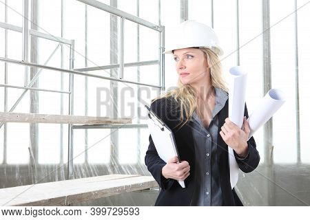 Woman Architect Or Construction Engineer Wear Helmet And Holds Folder And Blueprint Inside A Buildin