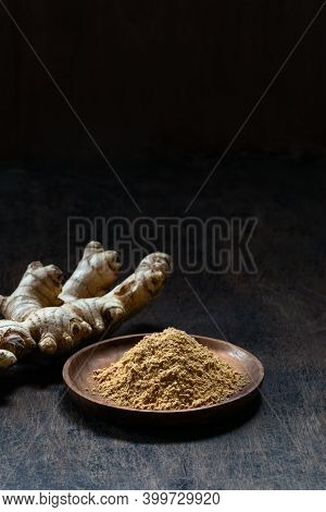Fresh Organic Ginger Root And Powder In Wooden Bowl On Dark Old Rustic Background With Copyspace Ver