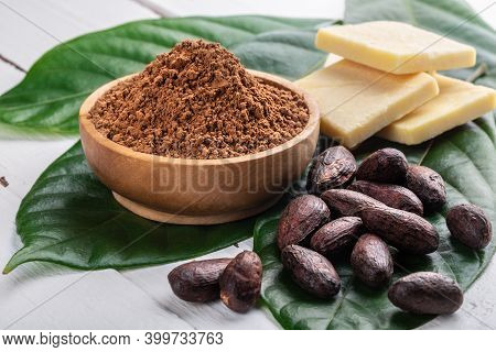 Cacao Powder In Wooden Bowl, Whole Cacao Beans, Pieces Of Cocoa Butter With Original Fresh Leaves On