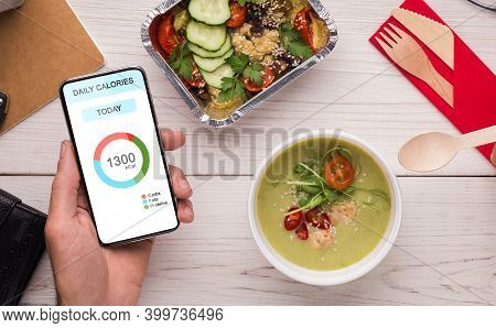 Healthy Eating. Man Using Daily Calories Counting App On Smartphone And Having Lunch At Workplace In