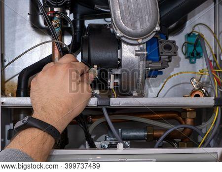 Plumber Repairing A Condensing Boiler In The Boiler Room.