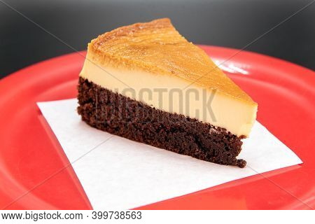 Chocolate Layer On Bottom Of Mexican Flan Dessert Cut Into A Wedge And Presented On A Red Plate.