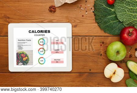 Calories Counter App Opened On Digital Tablet Flat Laying Next To Organic Fruits And Vegetables On W