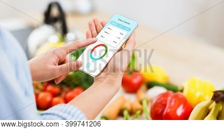 Woman Using Calorie Counter Application On Her Smartphone While Cooking Healthy Lunch In Kitchen. Fr
