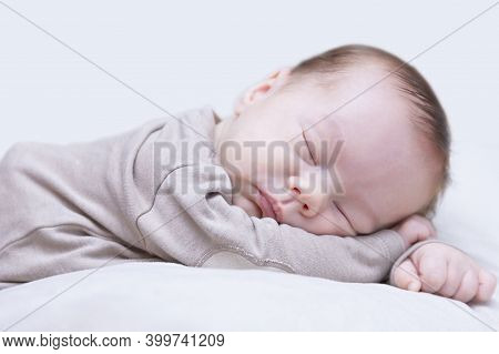 Newborn Sleeping Baby On A Light Background, Close-up, Lifestyle, Purity And Innocence Concept, Copy