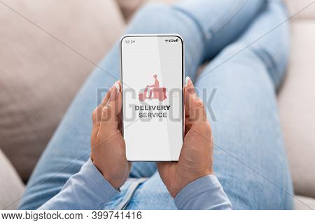 Woman Browsing Delivery Service App On Smartphone While Relaxing At Home, Browsing Modern Mobile App