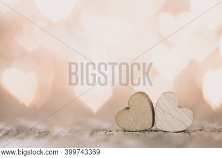 Two handmade wooden hearts on beautiful golden heart bokeh background. Vintage style. Love Valentine's Day concept.