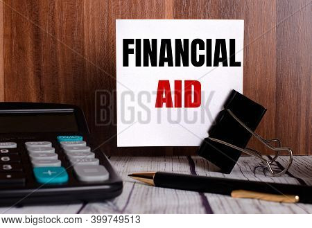 Financial Aid Is Written On A White Card On A Wooden Background Next To A Calculator And Pen.