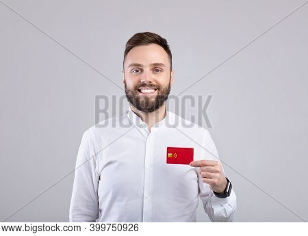 Positive Young Man In Formal Wear Showing Credit Card, Looking At Camera And Smiling On Grey Studio