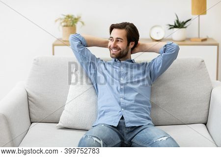 Relaxed Guy Sitting Holding Hands Behind Head On Sofa Relaxing At Home. Pleased Man Resting In Livin