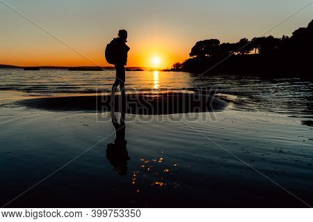Silhouette Of A Happy Joyful Woman Enjoying Sunset Nature View And Backpack Travelling At The Beach.