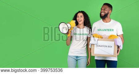 Volunteering And Charity. Female And Male Volunteers Holding Donation Box Collecting Clothes For Hom