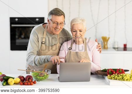 Senior Couple Cooking And Using Laptop Browsing Internet For Online Recipes Preparing Healthy Dinner