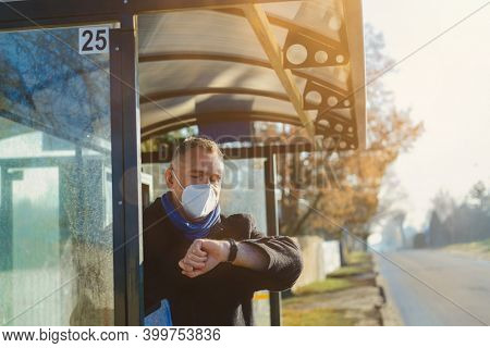 Man stands at the bus stop waiting for the bus in an antiviral mask