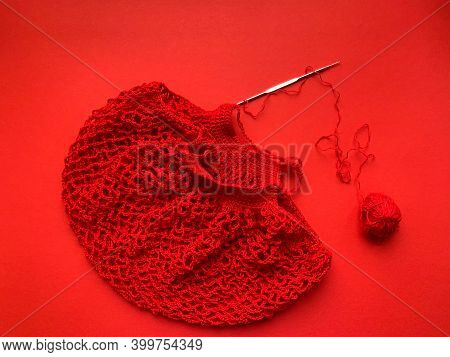 The Process Of Creating A String Bag. The String Bag Is Red. Reusable Shopping Bags On Red Backgroun