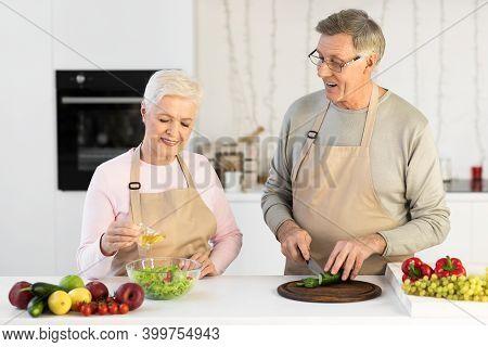 Senior Couple Enjoying Food Preparation Together Cooking Making Salad In Modern Kitchen Indoor. Matu