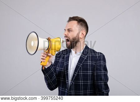 Confident Millennial Man In Formal Wear Shouting Into Megaphone On Grey Studio Background. Young Pub