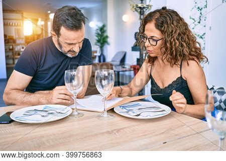 Middle age beautiful couple wearing casual clothes smiling happy. Sitting with smile on face reading restaurant menu.