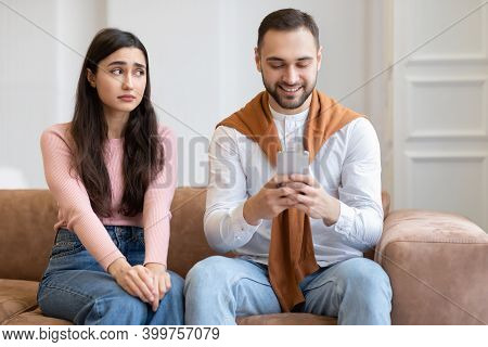 Sad Arab Wife Looking At Husband While He Texting On Cellphone Ignoring Her Sitting On Sofa At Home.