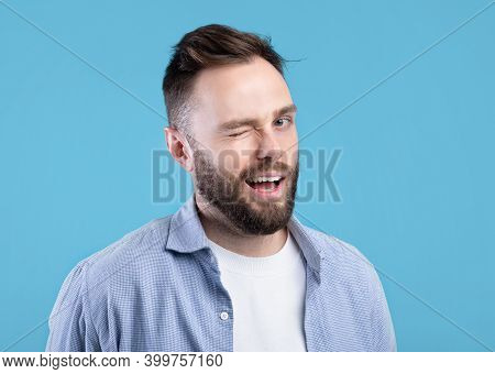 Confident Handsome Caucasian Man Winking And Smiling At Camera On Blue Studio Background. Playful Yo