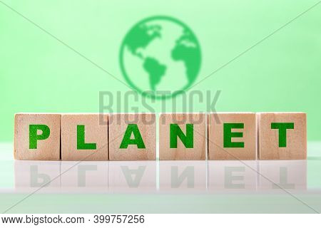 The Word Planet Written On Wooden Cubes Against On Light Green Background With Earth Icon. Save Plan