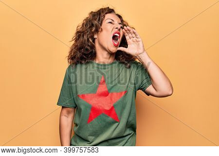 Middle age beautiful woman wearing t-shirt with red star revolutionary symbol of communism shouting and screaming loud to side with hand on mouth. Communication concept.