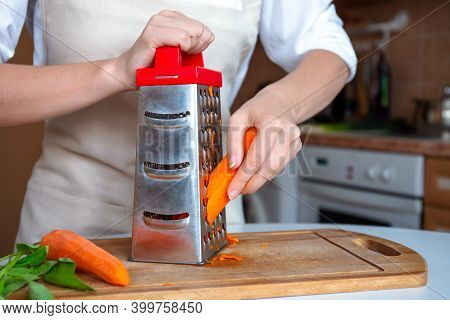 Female Hands Are Rubbing Fresh Orange Carrots On A Steel Silver Grater. Grated Carrots. Woman Chef P