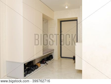 Beautiful Modern Entrance Hall In Light, White Colors With A Wardrobe, Hooks For Clothes, A Chest Of