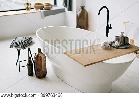 White Bathtub Fills With Foam Water In A Modern Apartment With Stylish Loft-style Interior Design, H
