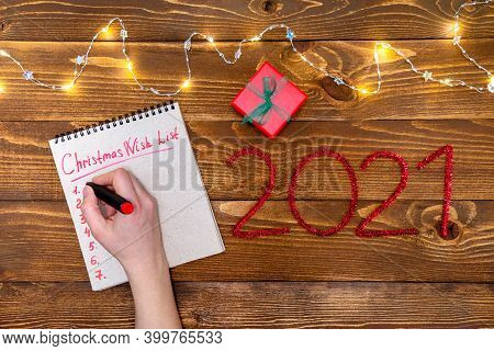 Christmas Composition Gift, Garland, Woman Hand Writes A Wish List And Numbers 2021. New Year On A W