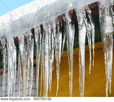 A Close-up Of Large Frozen Icicles From A Snow Covered Roof With A Broken Rain Gutter In Winter.
