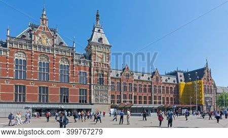 Amsterdam, Netherlands - May 14, 2018: Travelers In Front Of Central Train Station Building In Amste
