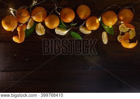 Whole Fruit Tangerines, Tangerine Slices, Tangerine Peel, Green Leaves On A Brown Wooden Table.