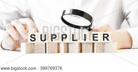 Businessman Holding Magnifier And Wood Block. Businessman Watch On The Wooden Cubes With Text Suppli