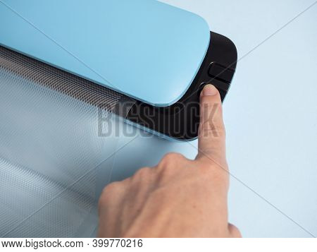 Close-up Of A Woman's Hand Pressing The Button Of A Blue Vacuum Packer. Concept Of Devices For Food