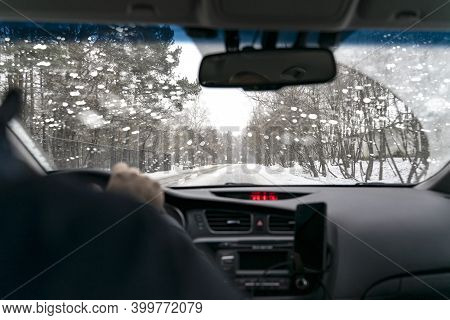 Car Drives On A Winter Road In A Blizzard. Inside View. Poor Road Visibility. Snow In The Windshield