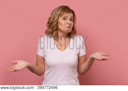 Clueless Mature Woman Shrugging Helpless With Her Shoulders.