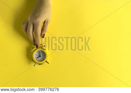 Ringing Twin Bell Vintage Classic Alarm Clock In Female Hand Isolated On Yellow Background. Rest Hou
