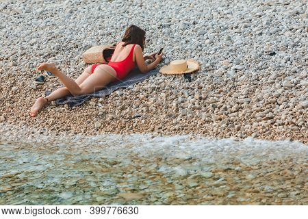 Young Pretty Sexy Woman Laying At Rocky Beach Suntanning