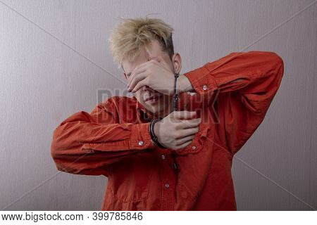 Portrait Of A Teenager In Handcuffs, Covering His Face With His Hands On A Gray Background, Medium P