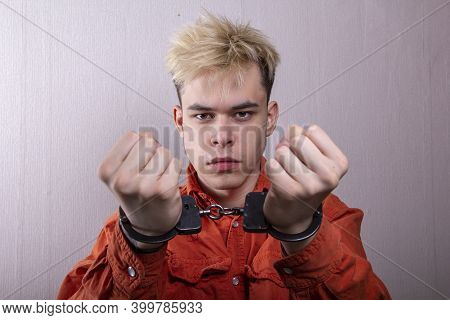A Handcuffed Teenager With An Angry Expression Stretches Out His Hands In Front Of A Gray Background