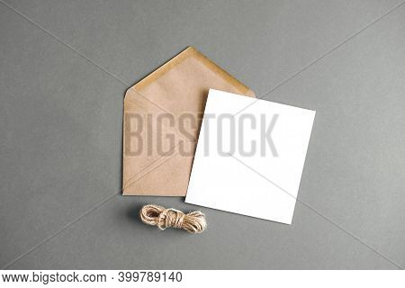 Envelopes With A White Letter Sheet On A Grey Background. The Envelopes Are Kraft Paper. Popular Col